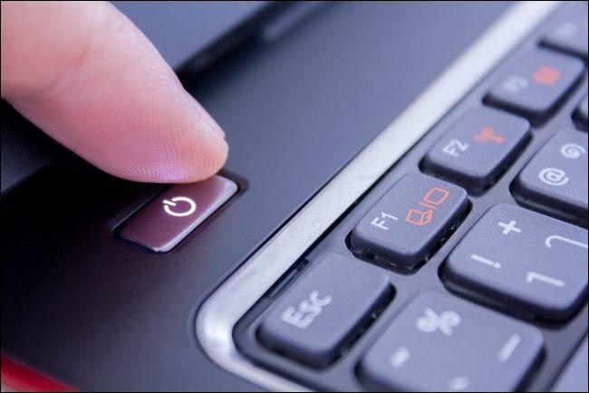 Un dedo presionando el botón de encendido en una computadora portátil para apagarlo.