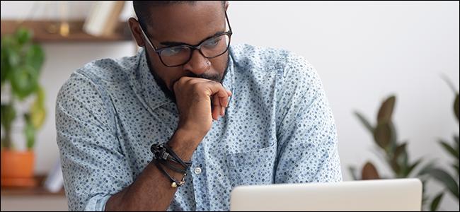 Un hombre se tapa la boca con la mano y mira la pantalla de una computadora portátil.