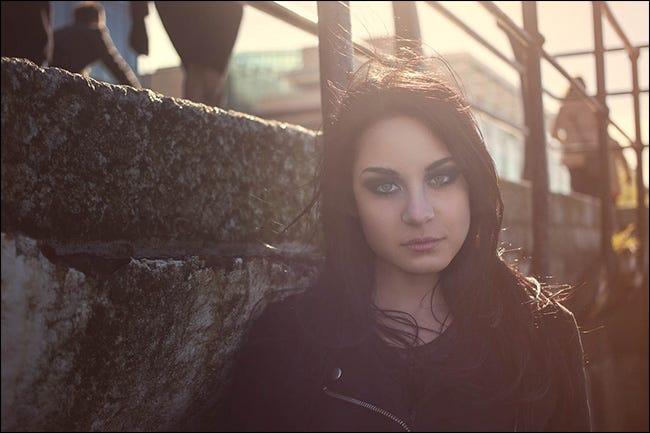 Retrato de una niña con el sol detrás de ella, creando un destello de lente.