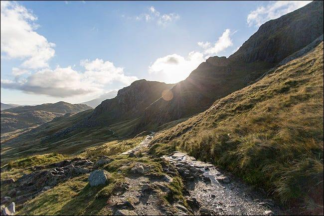 El sol brilla sobre una montaña, creando un destello de lente.