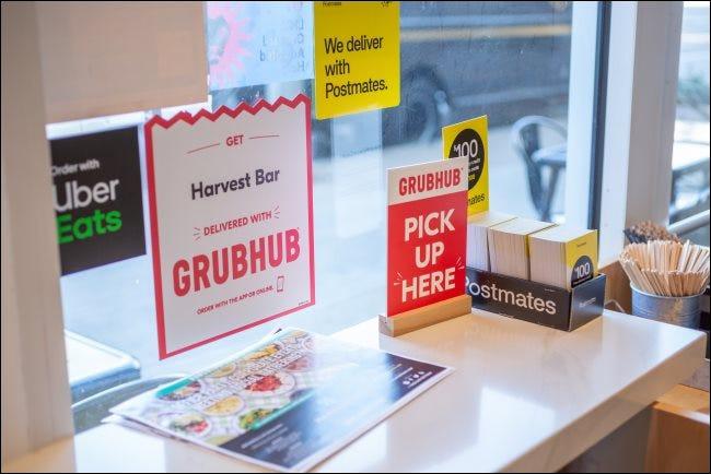 Letreros para GrubHub, Postmates y Uber Eats en un restaurante.