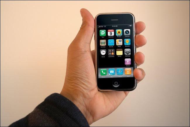 Mano sosteniendo un iPhone de primera generación.