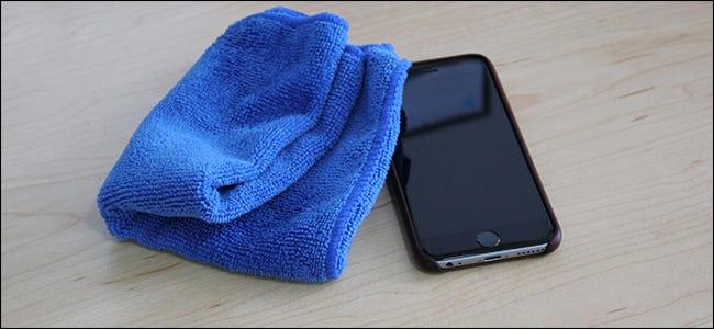 Un paño de microfibra azul junto a un iPhone.